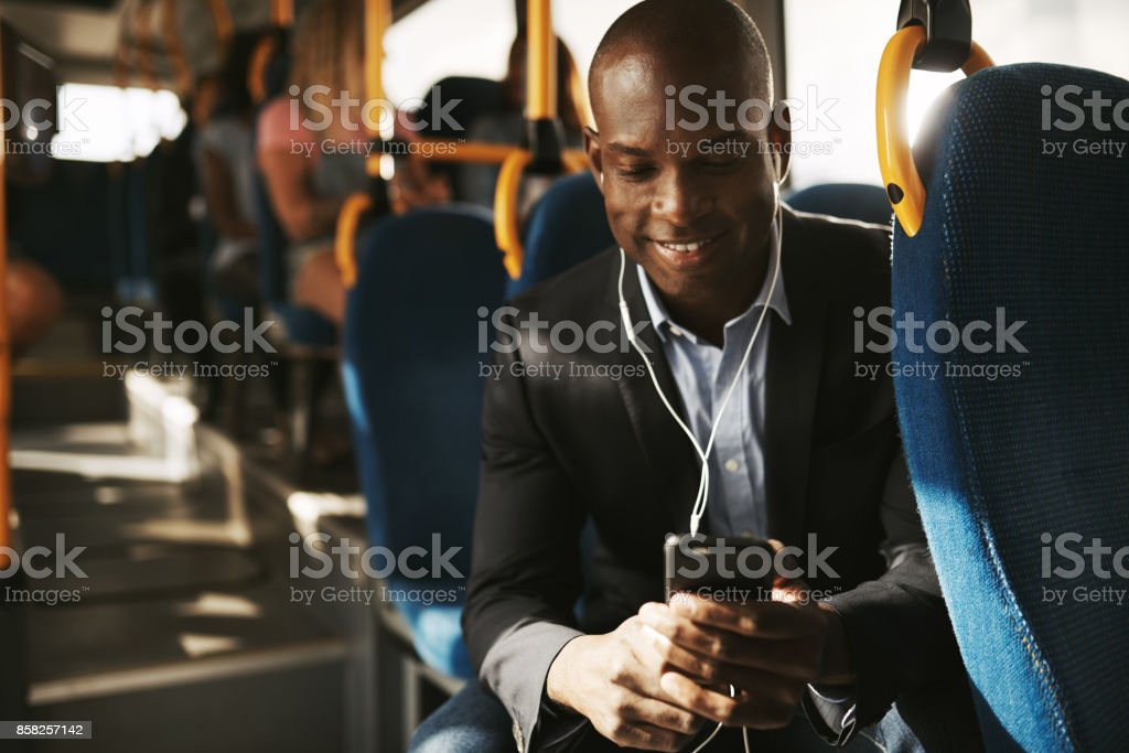 Smiling young businessman listening to music on his morning commute stock photo
