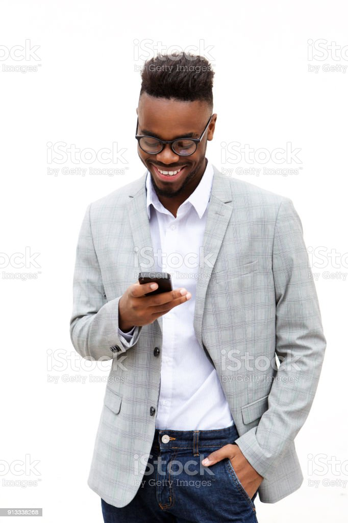 smiling young businessman looking at mobile phone stock photo