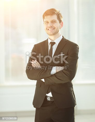 825082848istockphoto smiling young businessman on blurred background office 970338538