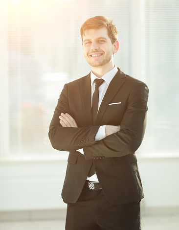 825082848 istock photo smiling young businessman on blurred background office 970338538