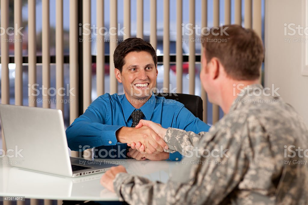 Smiling young businessman shaking hands with a soldier stock photo