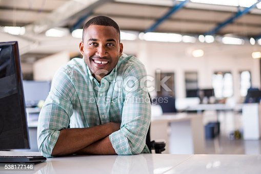 istock Smiling young businessman sitting at computer desk 538177146