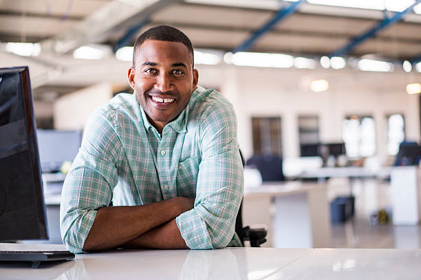 Smiling young businessman sitting at computer desk stock photo