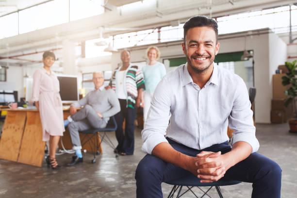 Smiling young businessman sitting with diverse colleagues in an office stock photo