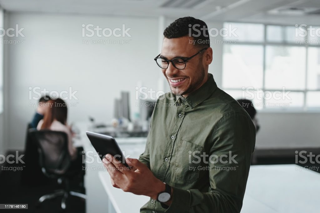 Smiling young businessman touching smartphone and checking online information in the modern office - Стоковые фото Африканская этническая группа роялти-фри