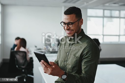 Confident smiling businessman using smartphone in office