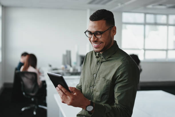 Smiling young businessman touching smartphone and checking online information in the modern office Confident smiling businessman using smartphone in office ipad stock pictures, royalty-free photos & images