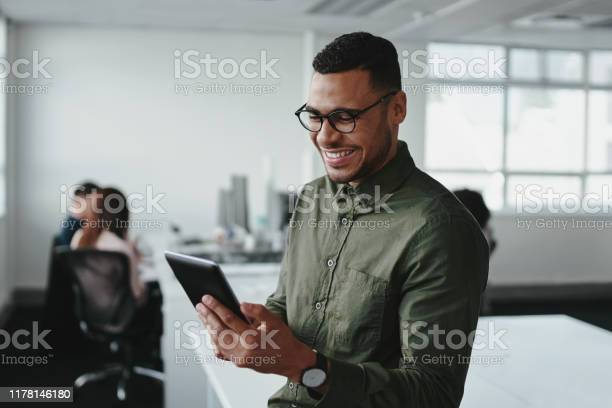 Smiling Young Businessman Touching Smartphone And Checking Online Information In The Modern Office — стоковые фотографии и другие картинки Африканская этническая группа