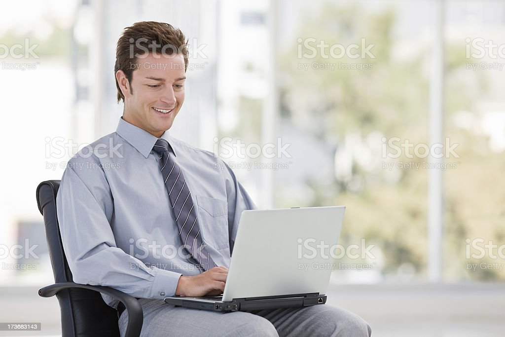 Smiling young businessman using laptop royalty-free stock photo