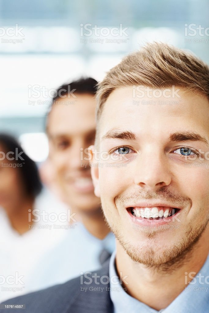 Smiling young businessman with colleagues in the background royalty-free stock photo