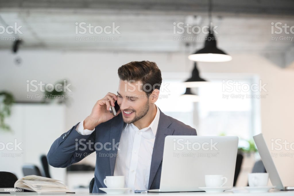 Smiling young businessman working in office Smiling young businessman sitting at office table and talking on mobile phone 25-29 Years Stock Photo