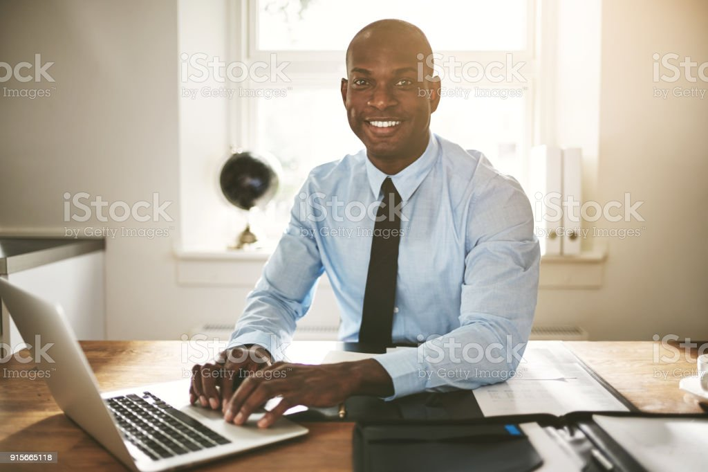 Smiling young businessman working on a computer at his desk stock photo