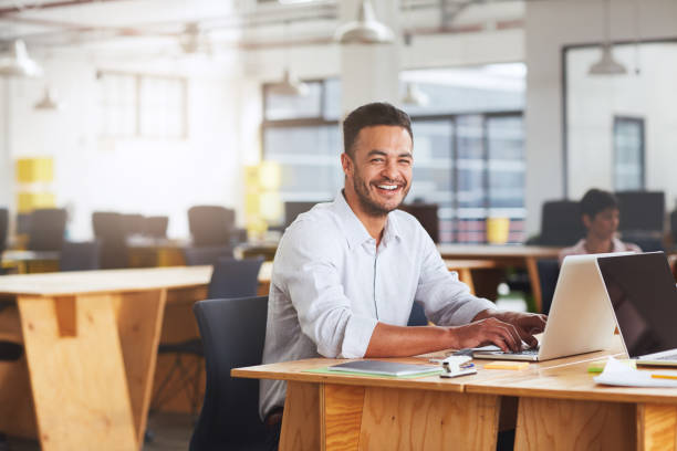 Smiling young businessman working on a laptop at his desk stock photo