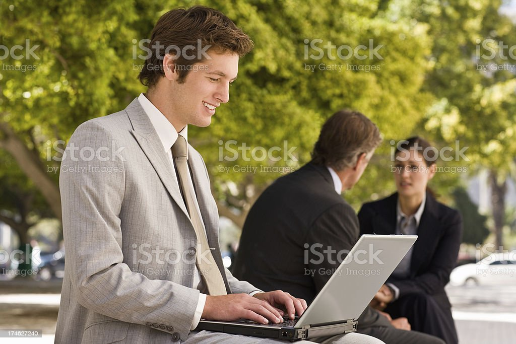 Smiling young businessman working on laptop royalty-free stock photo