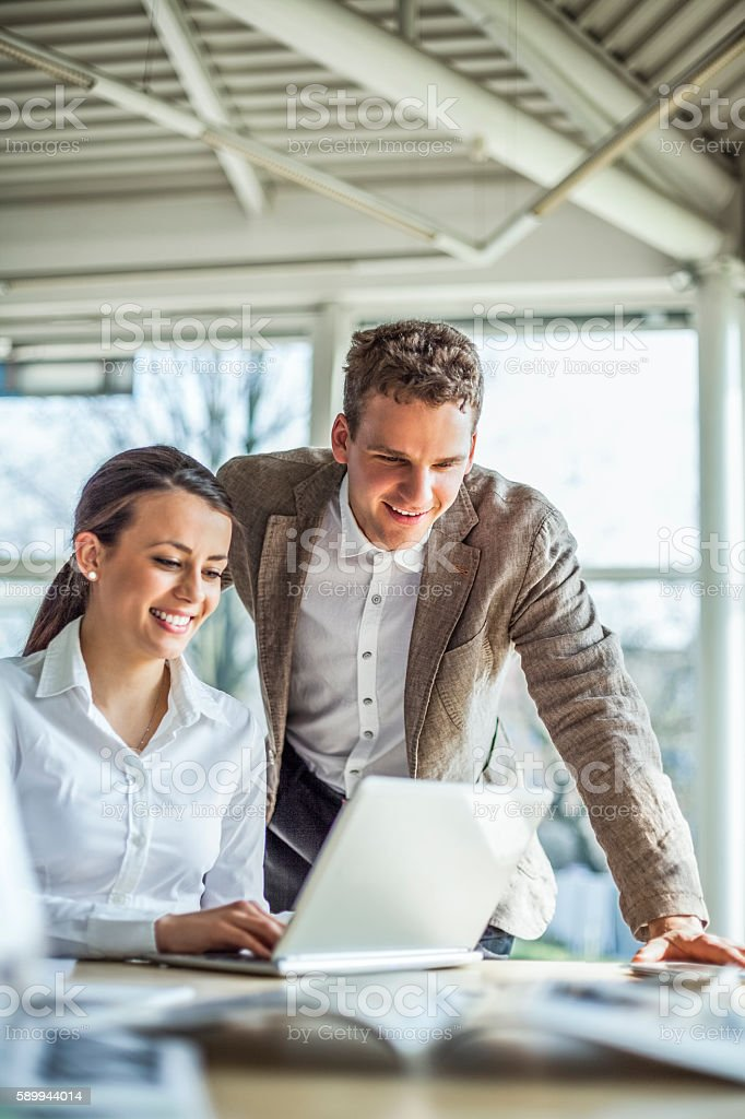 Smiling young businesspeople discussing over laptop at desk in office stock photo