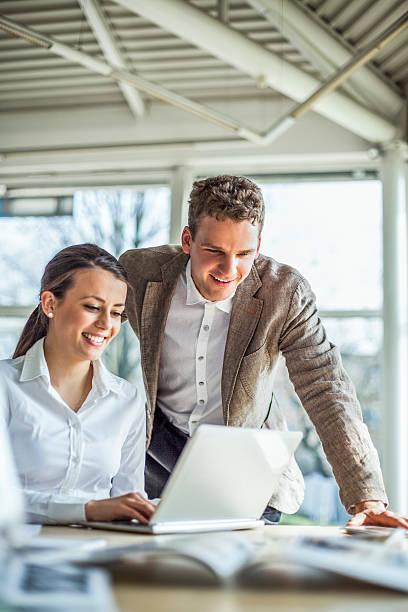 Lächelnde junge Geschäftsleute diskutieren über Laptop am Schreibtisch im Büro – Foto