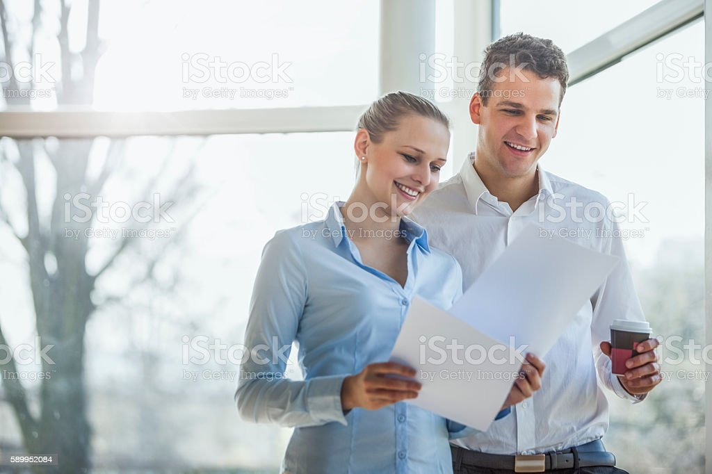 Smiling young businesspeople reviewing documents in office – Foto