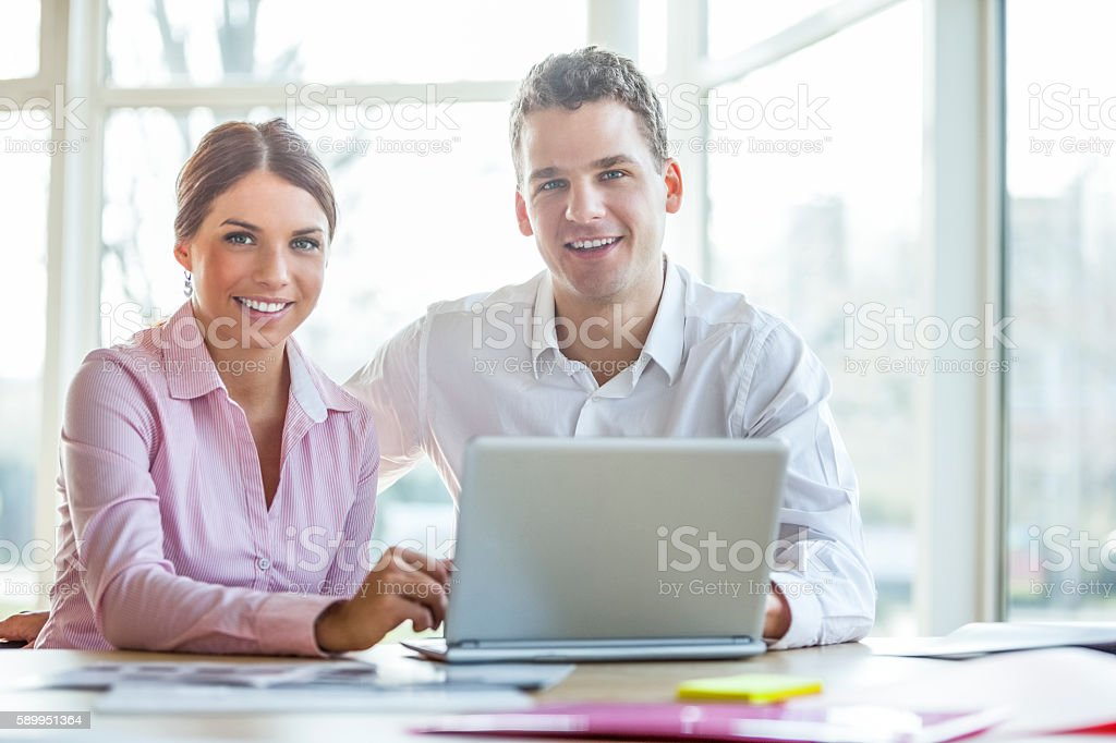Smiling young businesspeople using laptop at desk in office – Foto