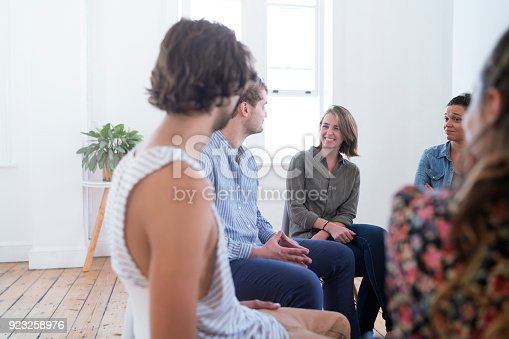 istock Smiling young businesswoman during group therapy 923258976
