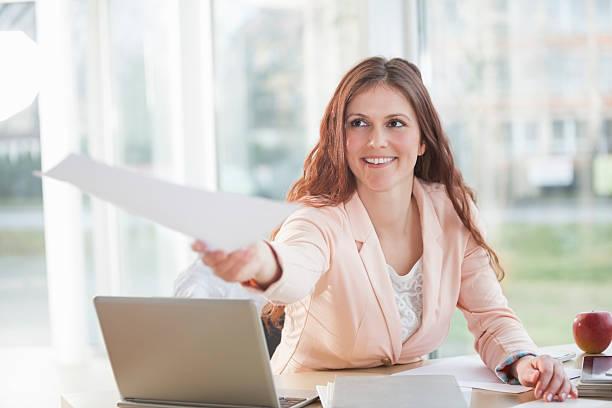 Lächelnde junge Geschäftsfrau gibt Dokument während sitzen am Schreibtisch – Foto