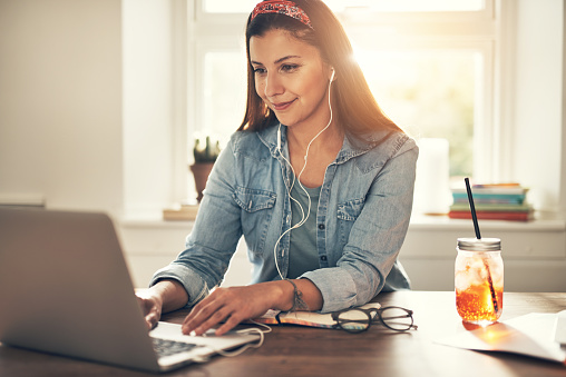 Pretty cheerful young female entrepreneur browsing laptop in headphones at workplace in office.