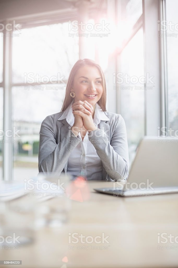 Smiling young businesswoman looking away with laptop at office desk stock photo