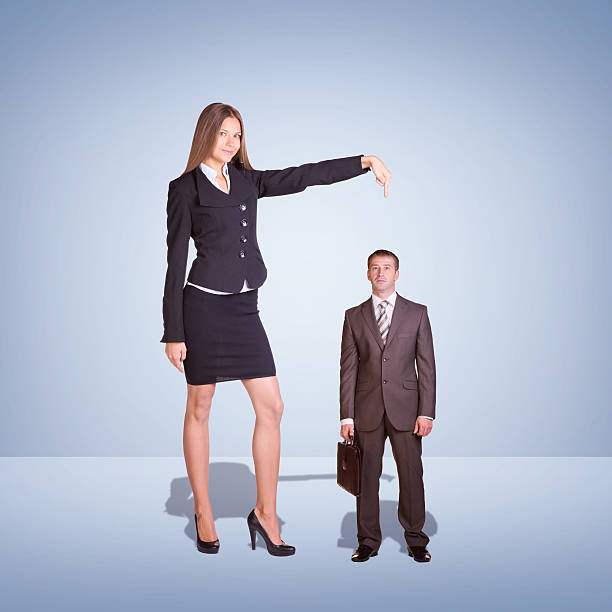 Smiling Young Businesswoman Pointing to small Businessman stock photo