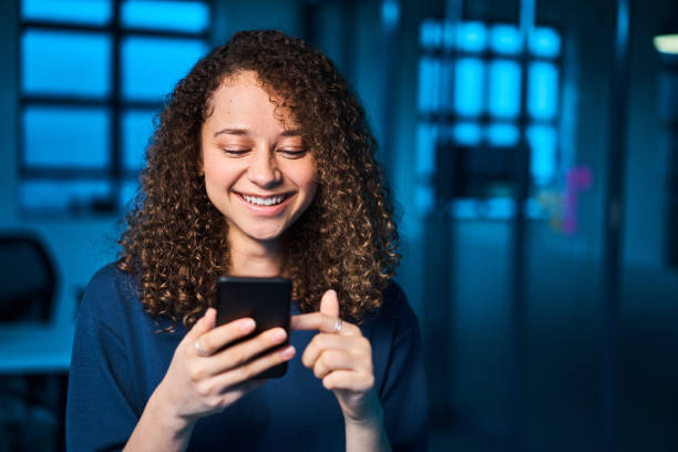 Smiling young businesswoman reading a text in an office at night stock photo