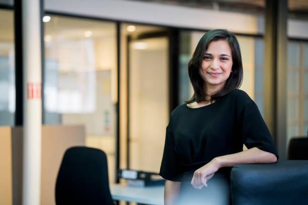 Lächelnde junge Geschäftsfrau, die durch Stuhl stehend – Foto
