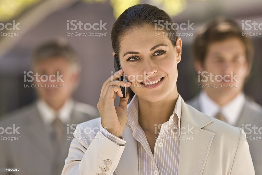 Smiling young businesswoman talking on cellphone royalty-free stock photo