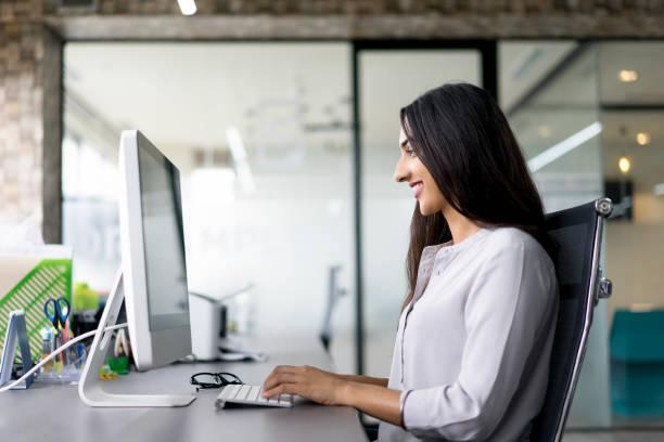 lächelnde junge geschäftsfrau, die eingabe auf computer - damen shirts online stock-fotos und bilder