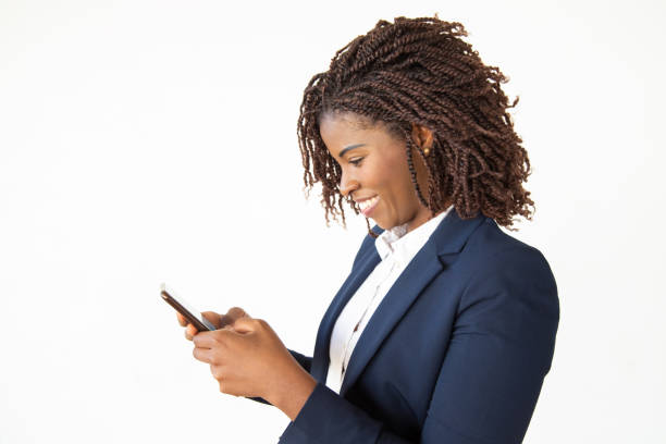 Smiling young businesswoman using smartphone stock photo