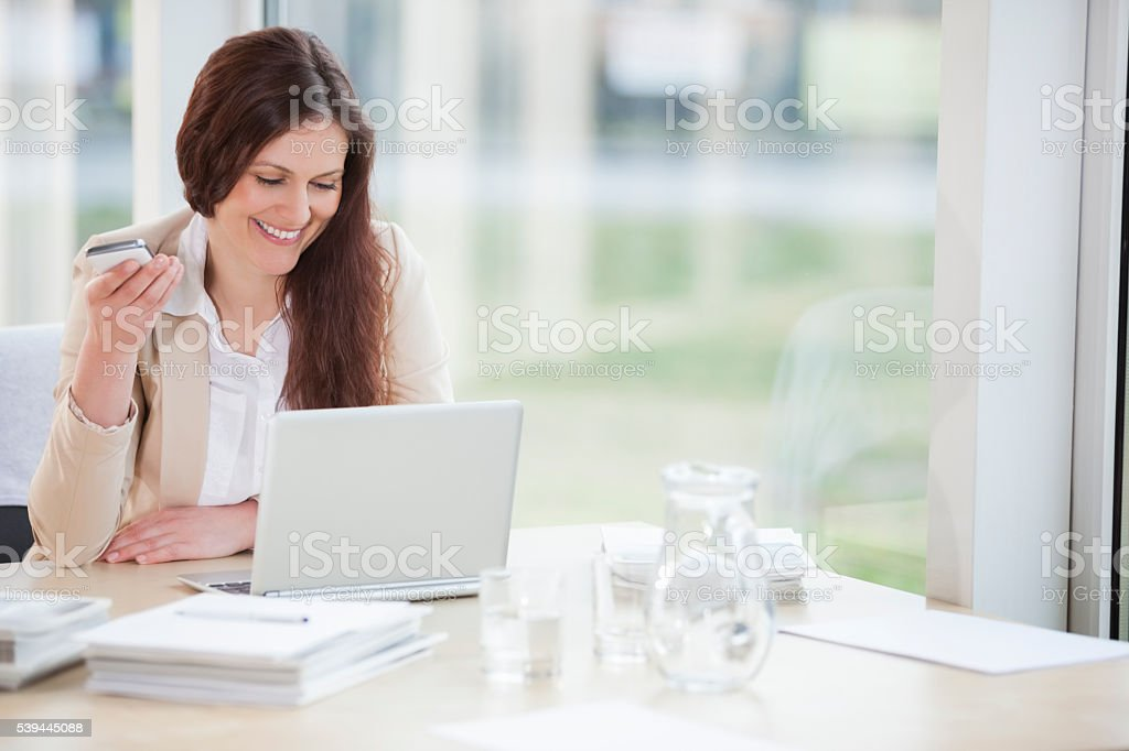 Smiling young businesswoman using technologies at office desk stock photo