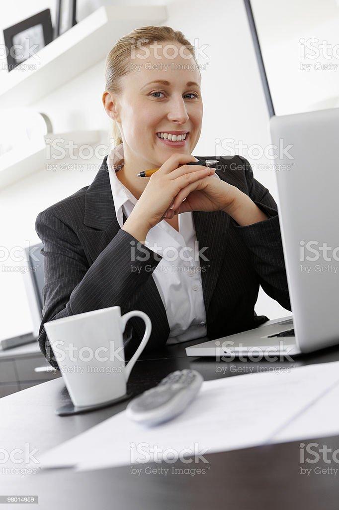 Sorridente giovane donna d'affari con un computer portatile a casa foto stock royalty-free