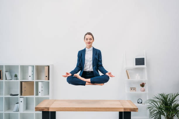 smiling young businesswoman with closed eyes meditating while levitating at workplace - gambe incrociate foto e immagini stock