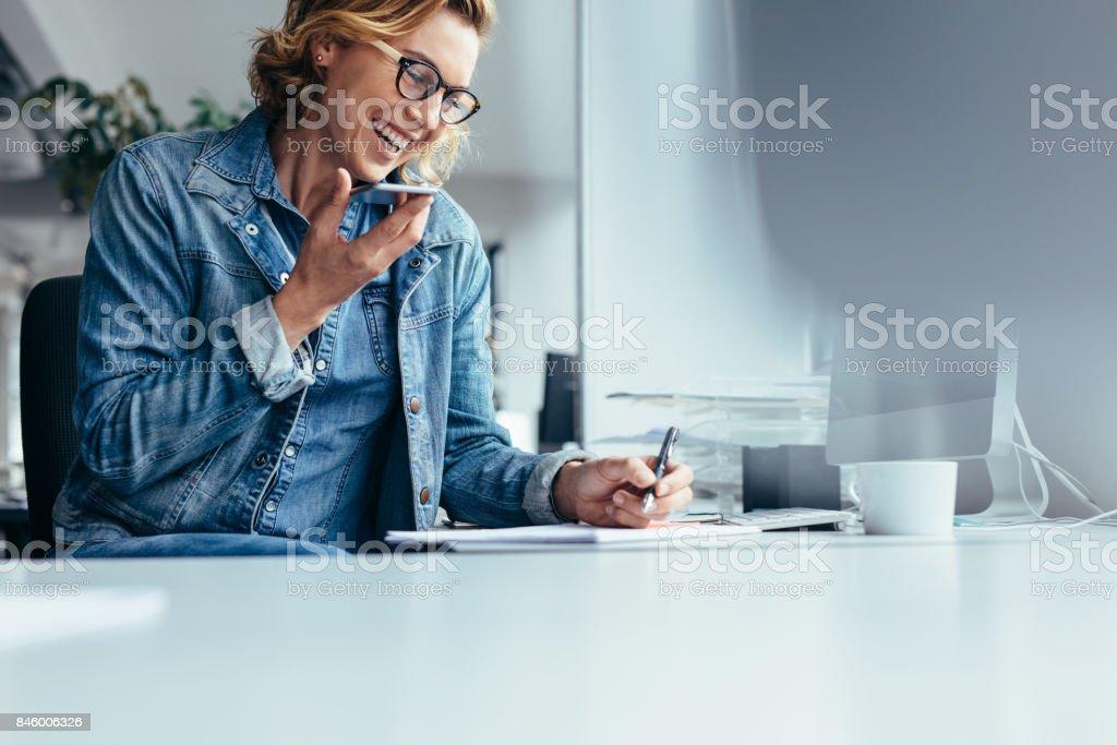 Sorrindo jovem Empresária trabalhando em sua mesa foto de stock royalty-free