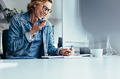 istock Smiling young businesswoman working at her desk 846006326