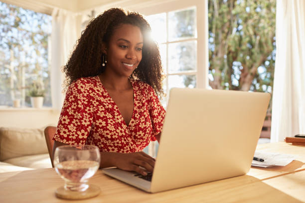 Smiling young businesswoman working from home on a laptop stock photo