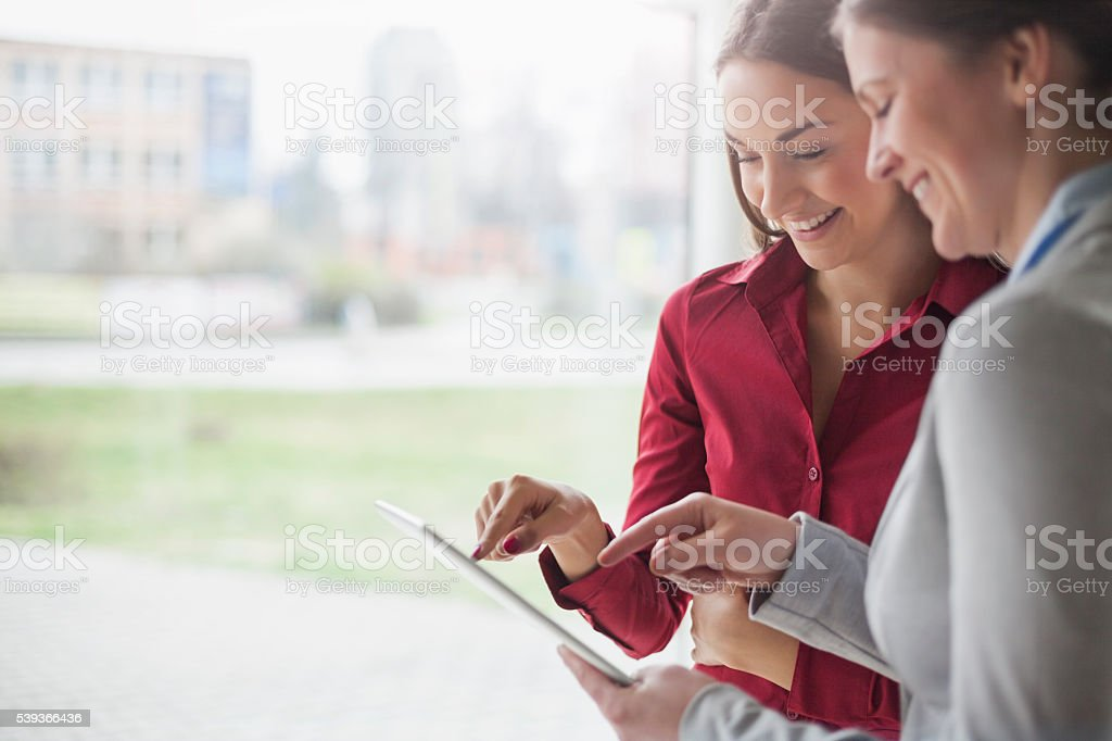 Smiling young businesswomen using tablet computer in office stock photo