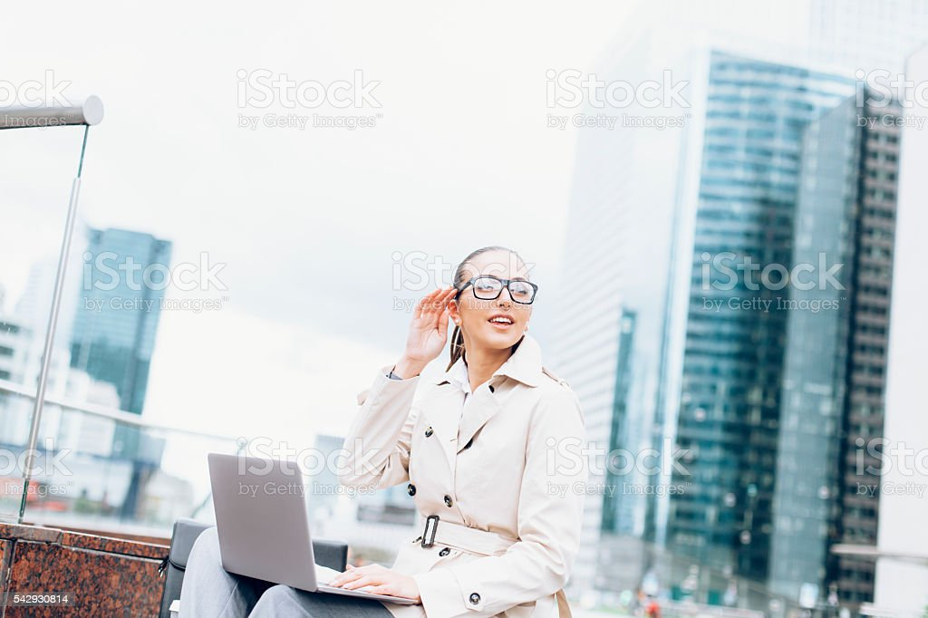 Smiling young bussineswoman sitting and using laptop stock photo
