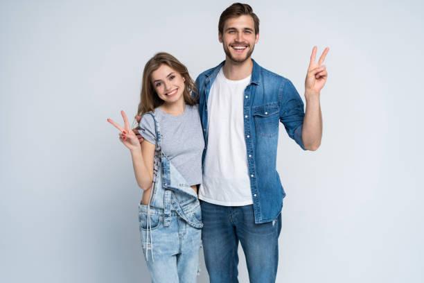lächelnde junge lässige Paar macht Sieg oder Friedenszeichen auf weißem Hintergrund. – Foto