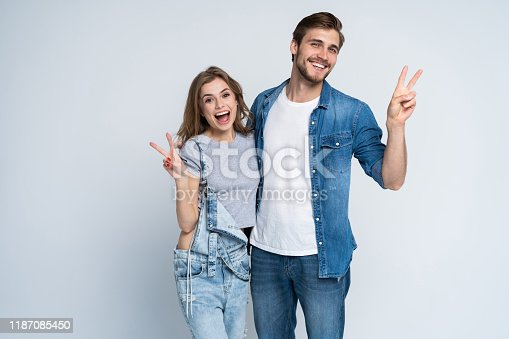 854381886 istock photo smiling young casual couple making victory or peace sign on white background. 1187085450