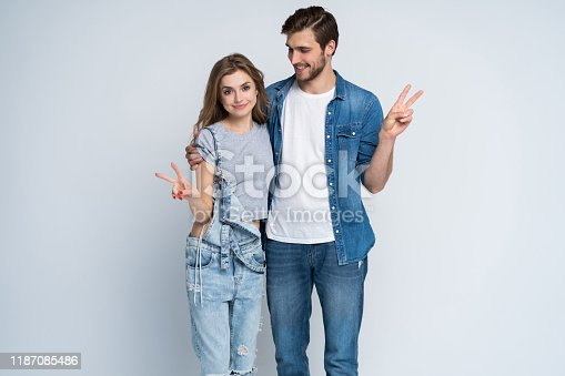 854381886 istock photo smiling young casual couple making victory or peace sign on white background. 1187085486