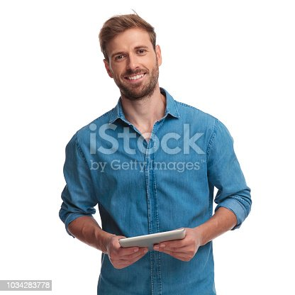 smiling young casual man holding a tablet pad computer on white background