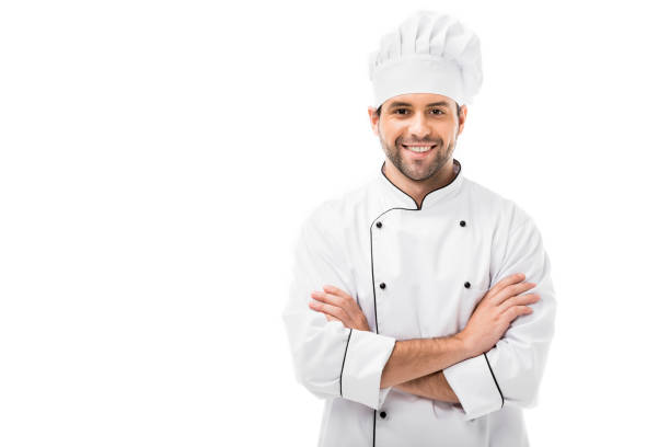 smiling young chef with crossed arms looking at camera isolated on white - chef zdjęcia i obrazy z banku zdjęć