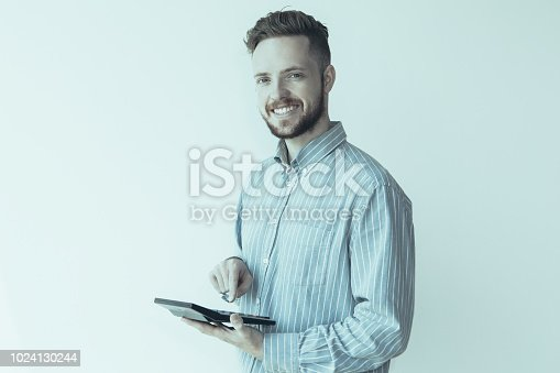 istock Smiling Young Clerk Calculating with Gadget 1024130244