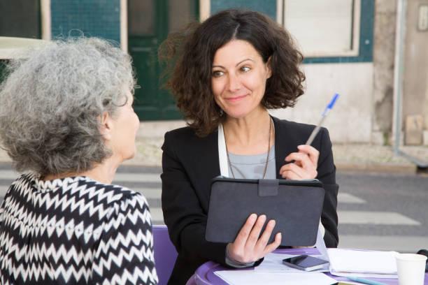 smiling young consultant offering pen to elderly client - senior business woman tablet imagens e fotografias de stock