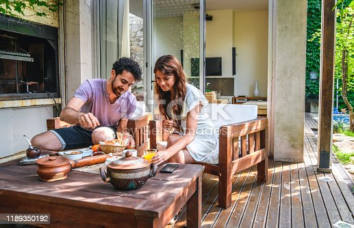 Hispanic woman in mid 20s and mixed race man in early 30s sitting side by side and enjoying breakfast on outdoor home deck.