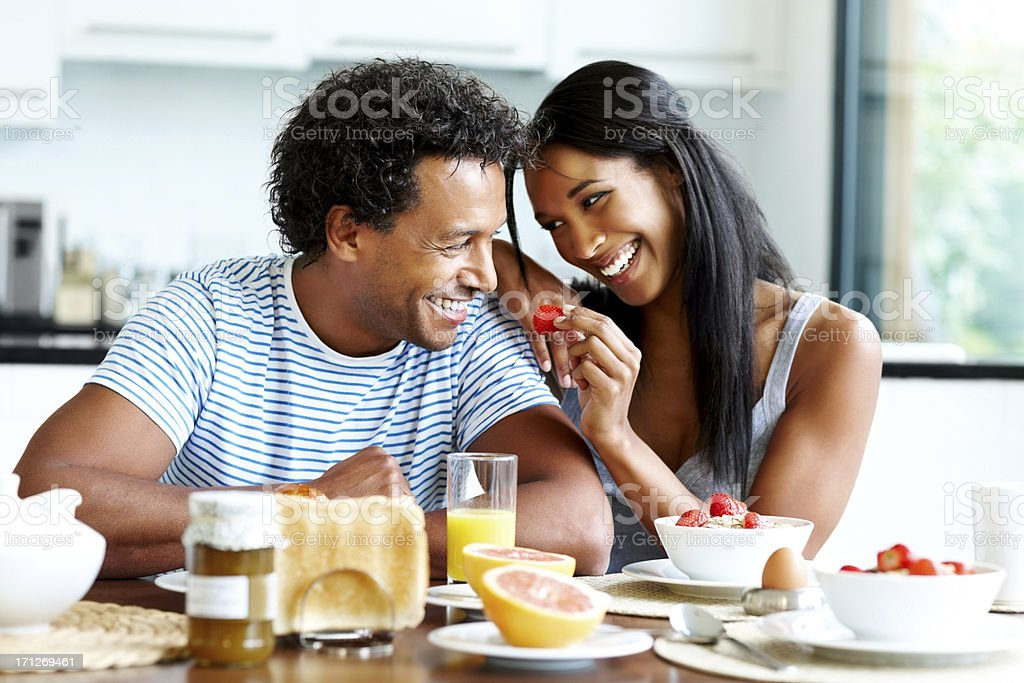 Smiling young couple enjoying breakfast royalty-free stock photo