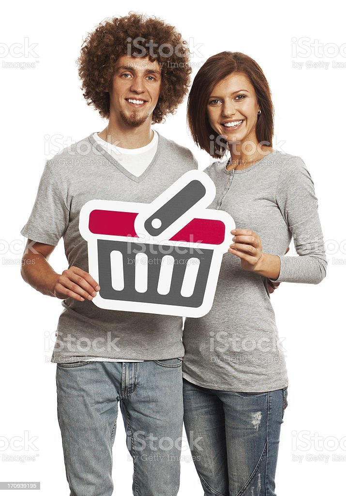 Smiling young couple holding shopping cart sign isolated on white. royalty-free stock photo